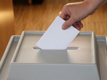 Stimmzettel wird in Wahlurne eingeworfen