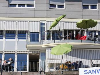Bewohner des Pflegeheims schauen vom Balkon aus dem Gottesdienst zu